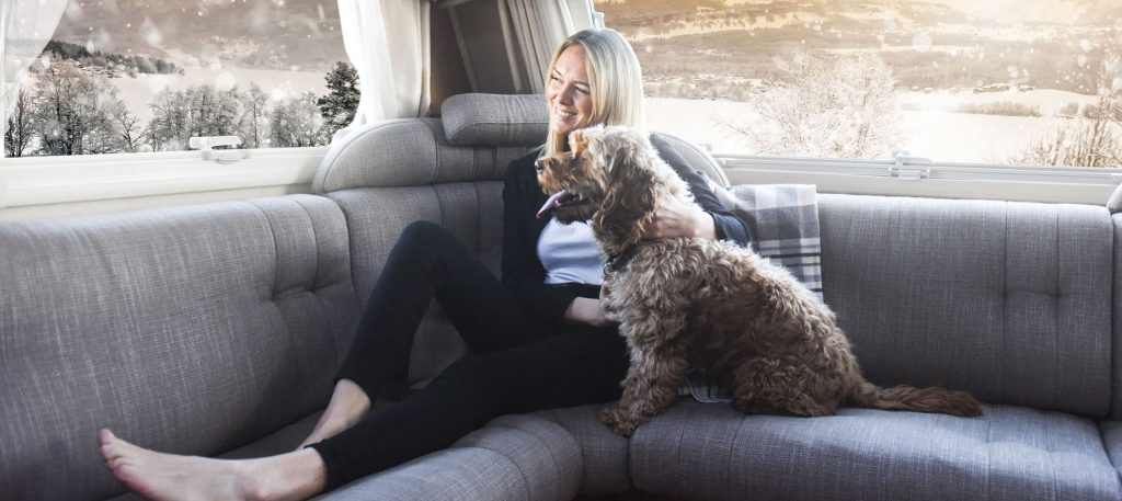 Lady relaxing in her motorhome with her dog